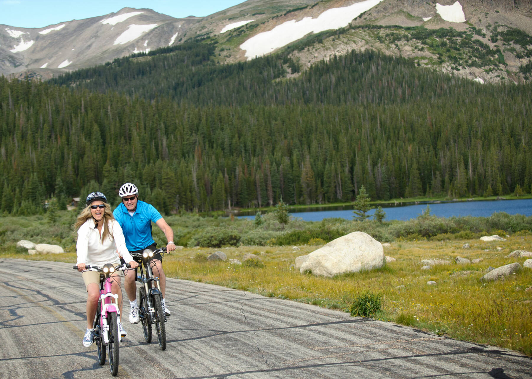 Couple riding optibikes with snowy mountains and lake in the background