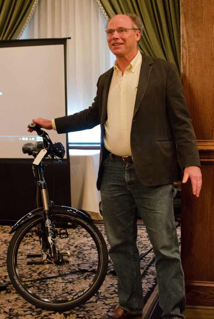 Jim Turner giving a talk standing next to an Optibike
