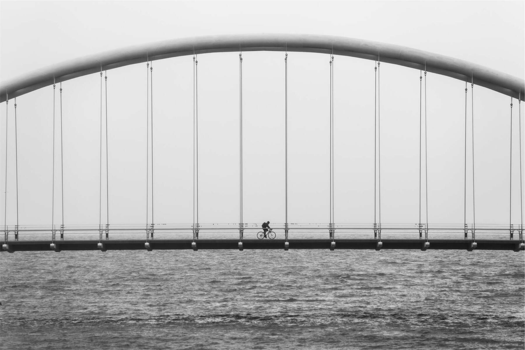 A bridge with a lone bicycle riding on it